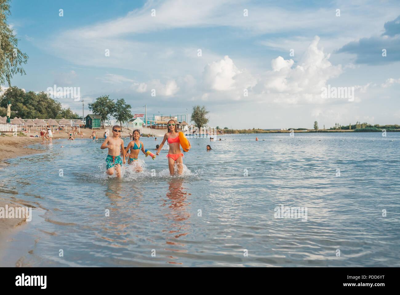 Felice poco gioiosa dei bambini che giocano in mare, con piacere gli spruzzi di acqua e di godersi le vacanze estive sul beach resort, viaggi e turismo c Immagini Stock