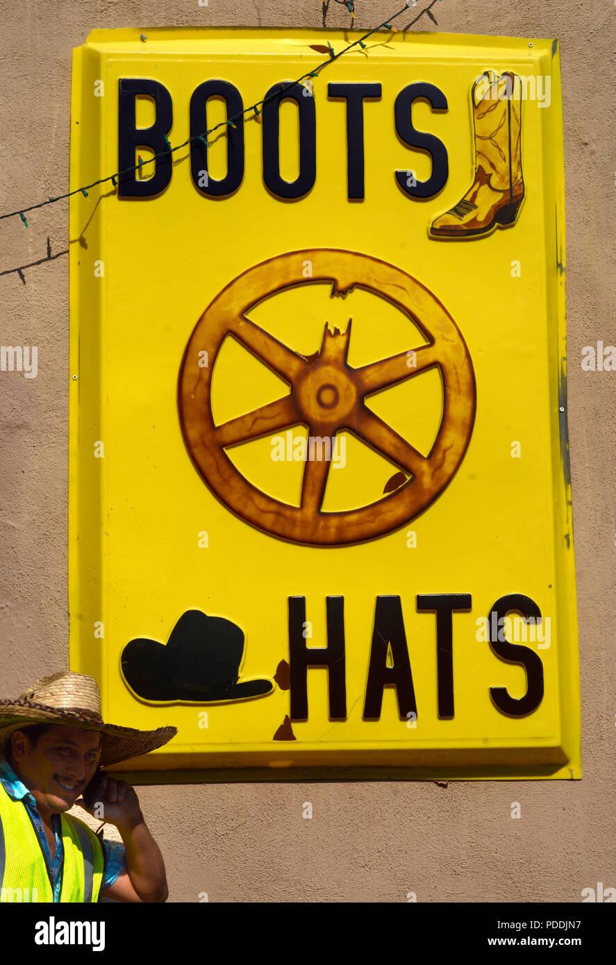 Un operaio colloqui sul suo smartphone accanto a un negozio vendita western  stivali e cappelli da c6c525874a3a
