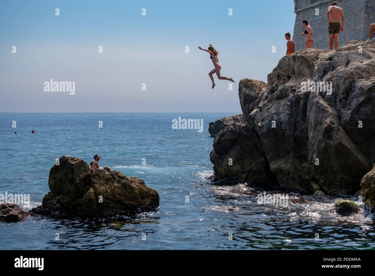 Persone che saltano fuori da una scogliera al mare Adriatico in Dubrovnik, Croazia, Europa Immagini Stock