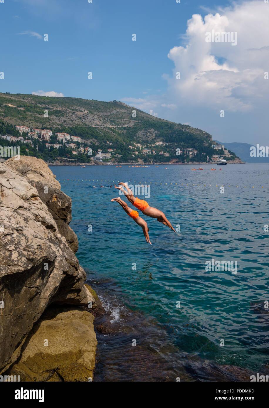 Il ragazzo si prepara a saltare da un dirupo nel mare Adriatico a Dubrovnik, Croazia, Europa Immagini Stock