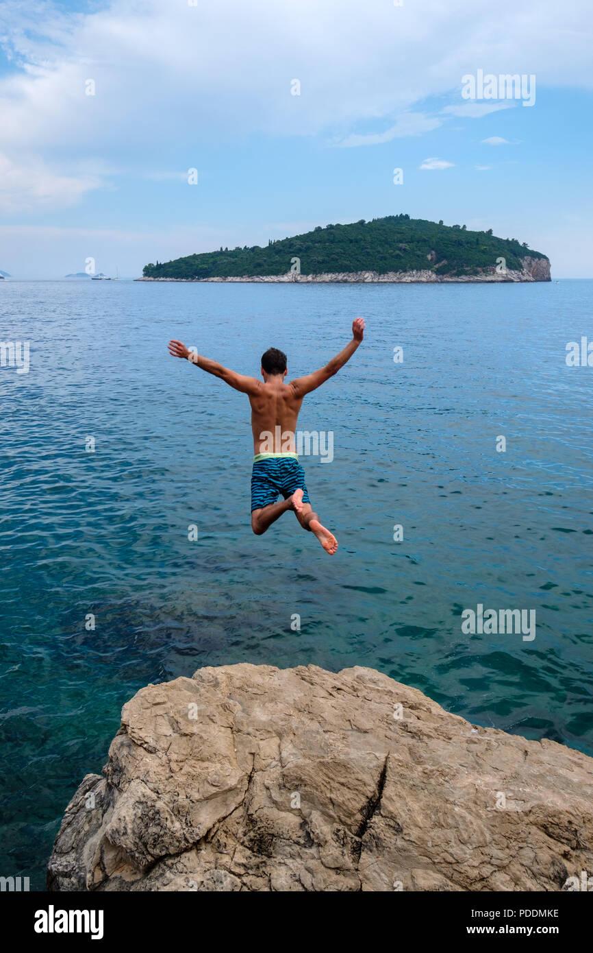 Persone che saltano fuori da una scogliera al mare Adriatico di fronte all'isola di Lokrum Dubrovnik, Croazia, Europa Immagini Stock