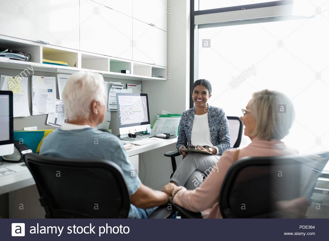 Medico donna parlando di coppia senior tenendo le mani in clinica office Immagini Stock