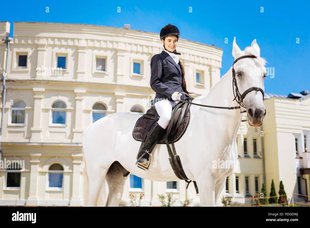 Eleganti Donna dolce cavalcare il suo cavallo bianco sulla grande pista Immagini Stock
