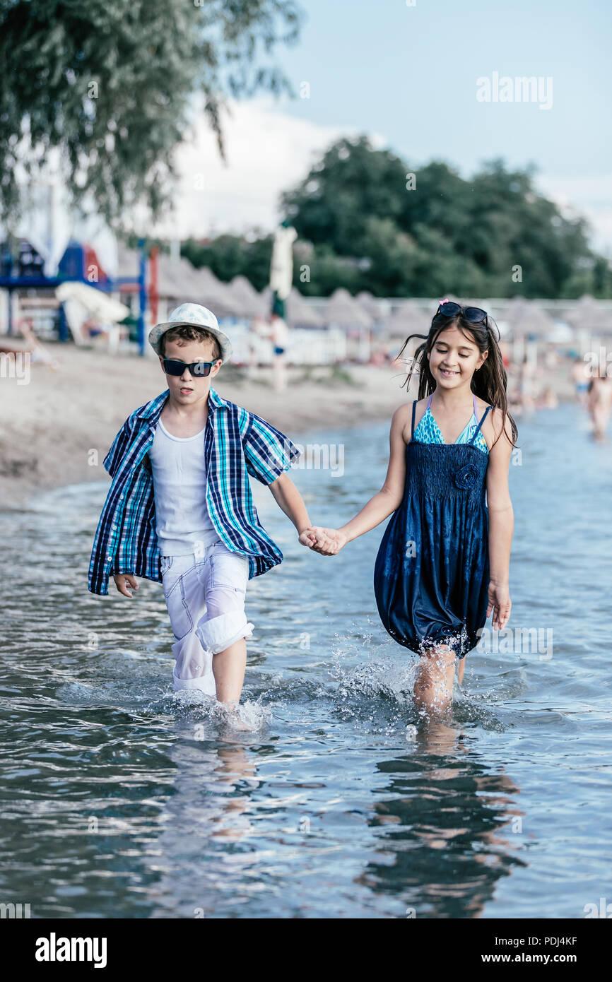 Dei bambini felici giocando in mare. Bambini il divertimento all'aperto. La vacanza estiva e uno stile di vita sano concetto Immagini Stock