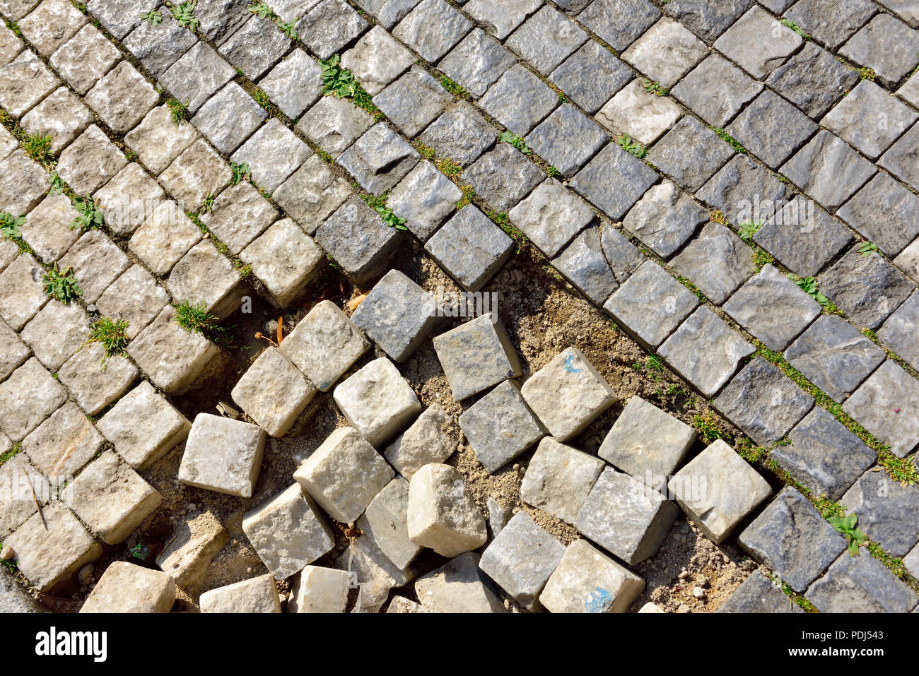 Pavimentazione in pietra con alcuni cubetti di granito perdere Foto Stock