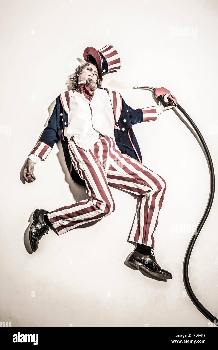 Lo zio Sam che giace morto accanto a una pompa di benzina ugello. Addicted a olio / combustibili fossili. Immagini Stock