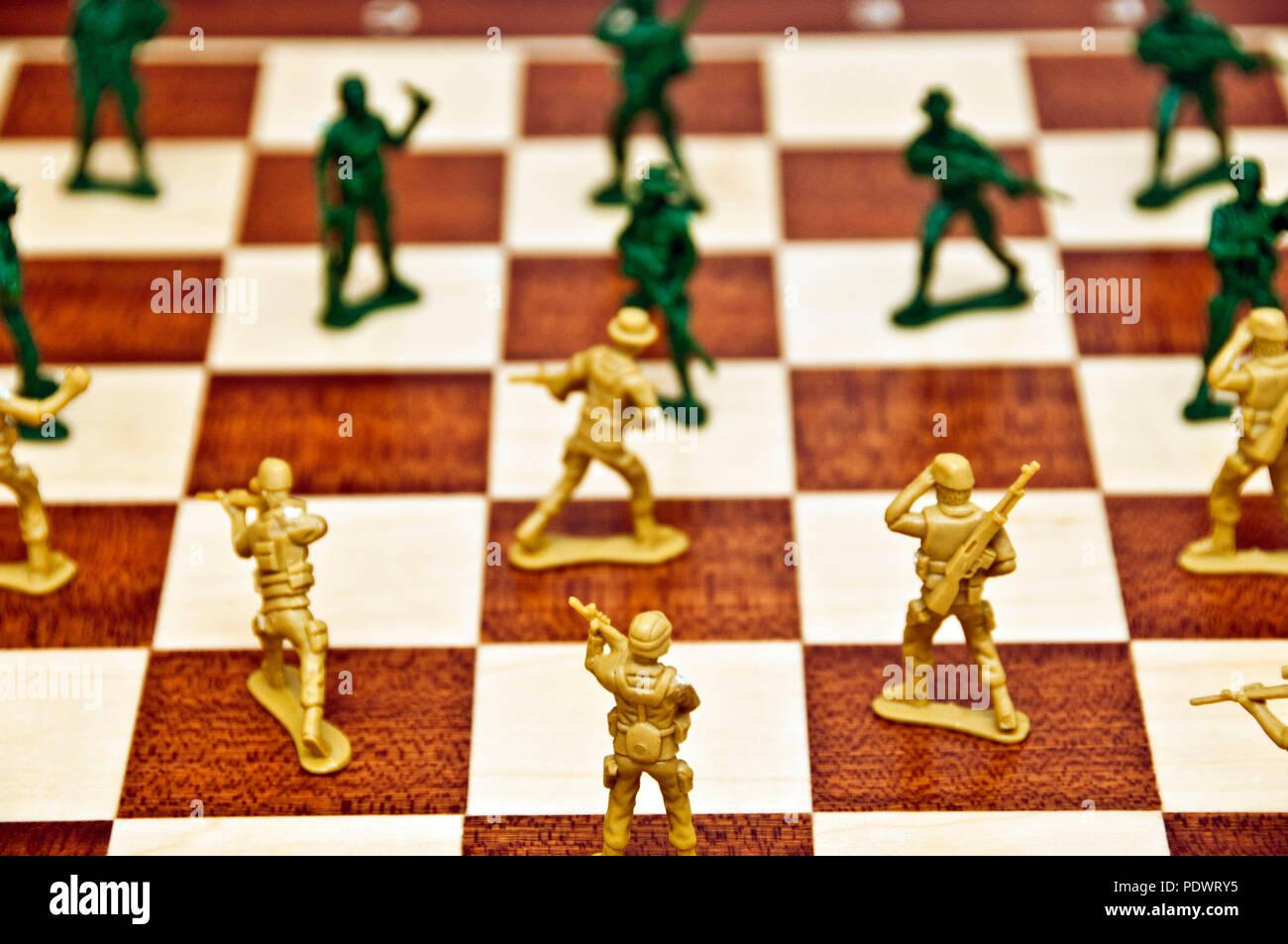 Giocattolo di plastica soldati su una scacchiera Immagini Stock