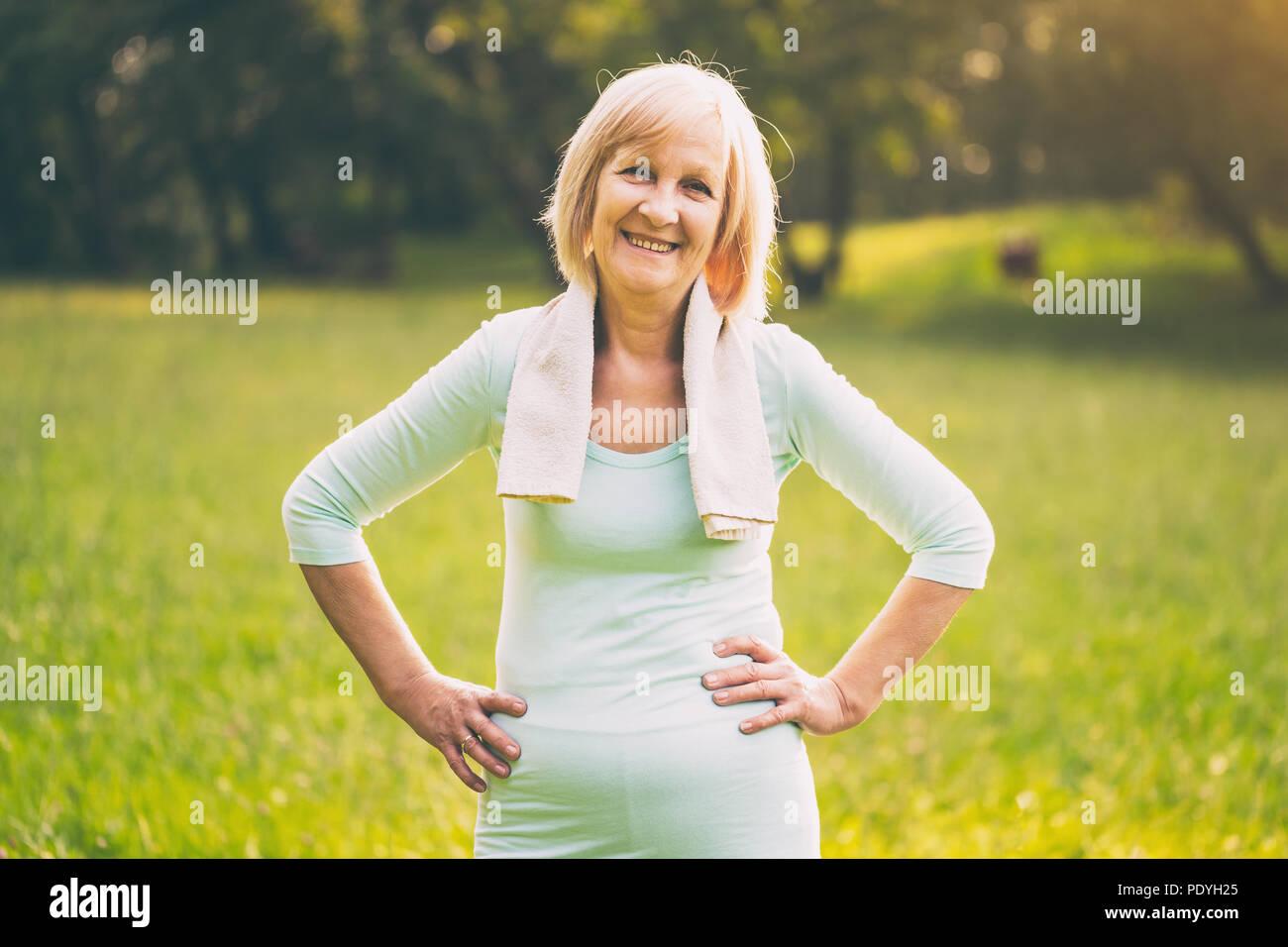Ritratto di senior sportivo donna in piedi nella natura.Immagine è intenzionalmente tonica. Immagini Stock