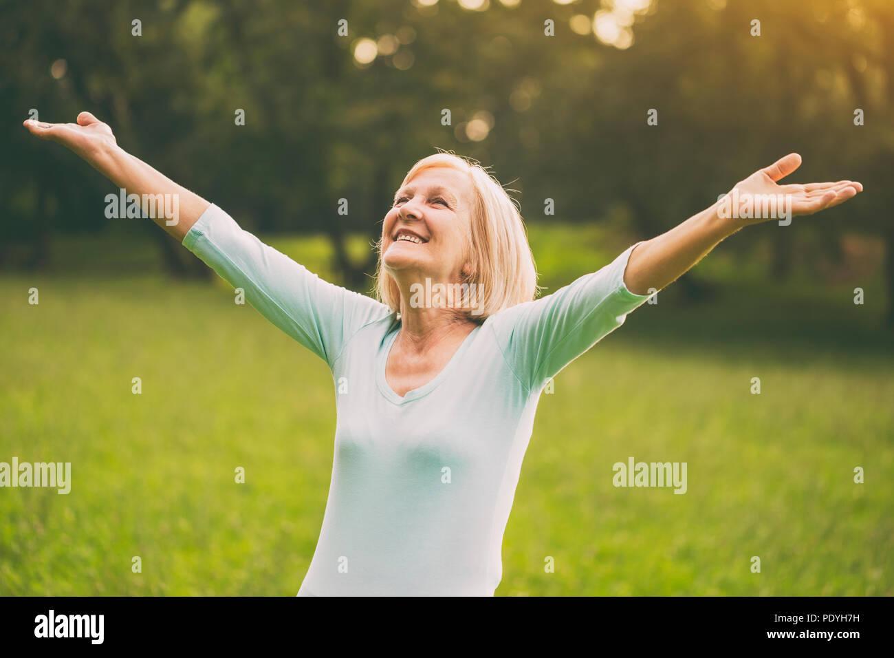 Senior donna gode con le braccia aperte in natura.Immagine è intenzionalmente tonica. Foto Stock