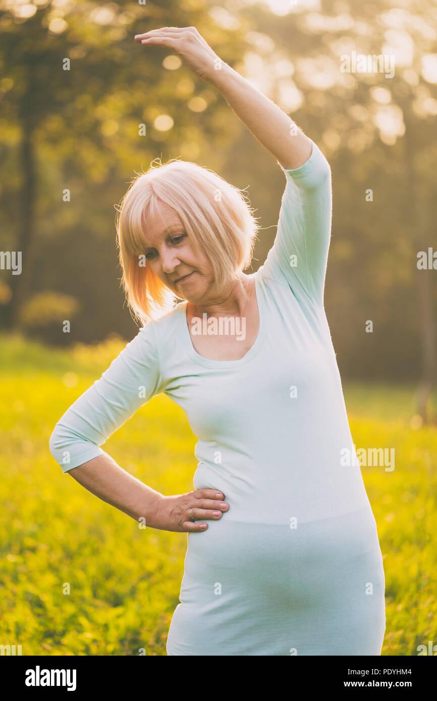 Sportivo da donna senior esercizio outdoor.Immagine è intenzionalmente tonica. Immagini Stock