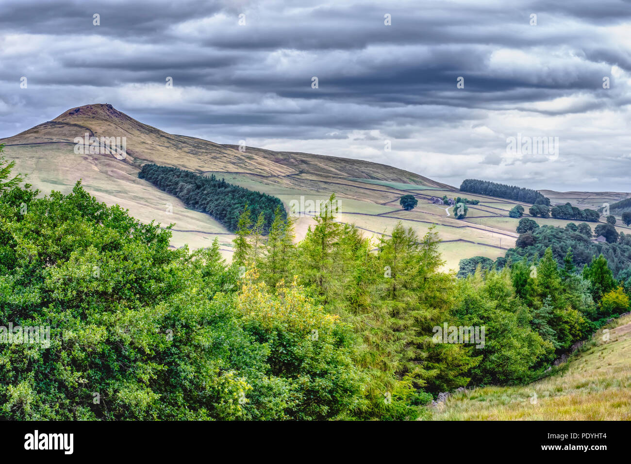 Idillico paesaggio del Parco Nazionale di Peak District, Derbyshire, Regno Unito.vista panoramica sulla valle di montagna con alberi in primo piano e il vertice in background. Immagini Stock