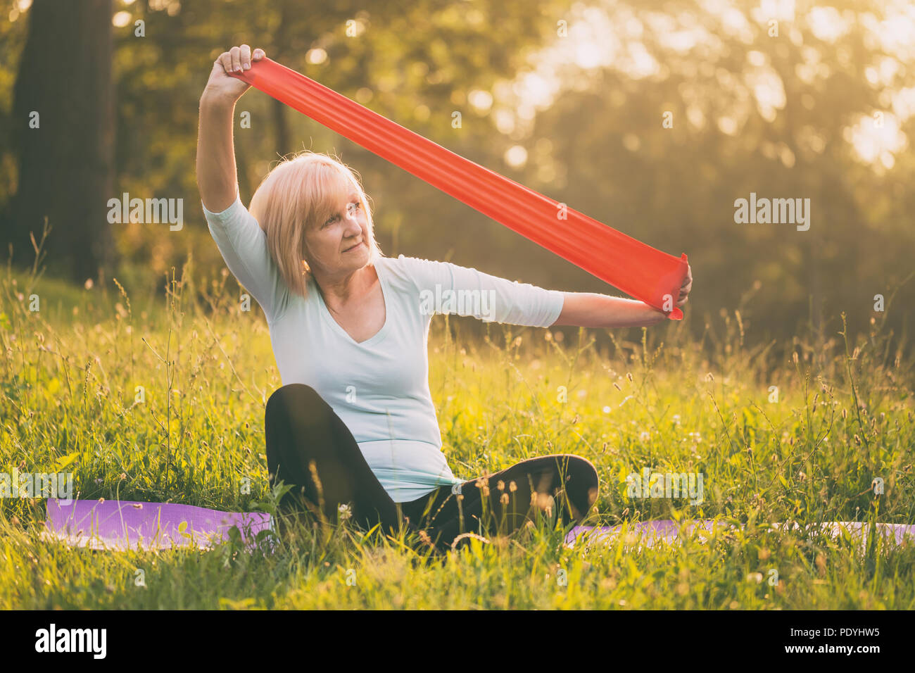Sportivo da donna senior esercitando con fascia di gomma all'aperto.Immagine è intenzionalmente tonica. Immagini Stock