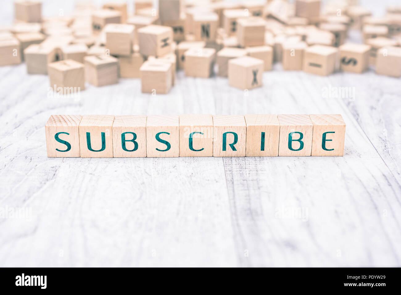La parola subscribe formata da blocchi di legno su un tavolo bianco, concetto di promemoria Immagini Stock
