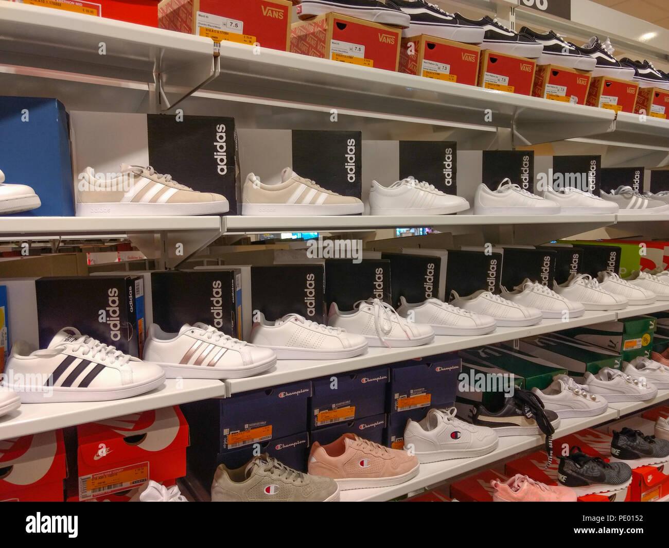 White scarpe Adidas visualizzati su scaffali in negozio