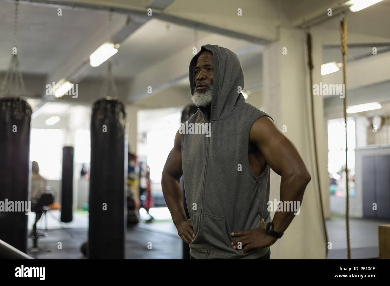 Senior uomo in felpa con cappuccio in piedi al centro fitness Immagini Stock