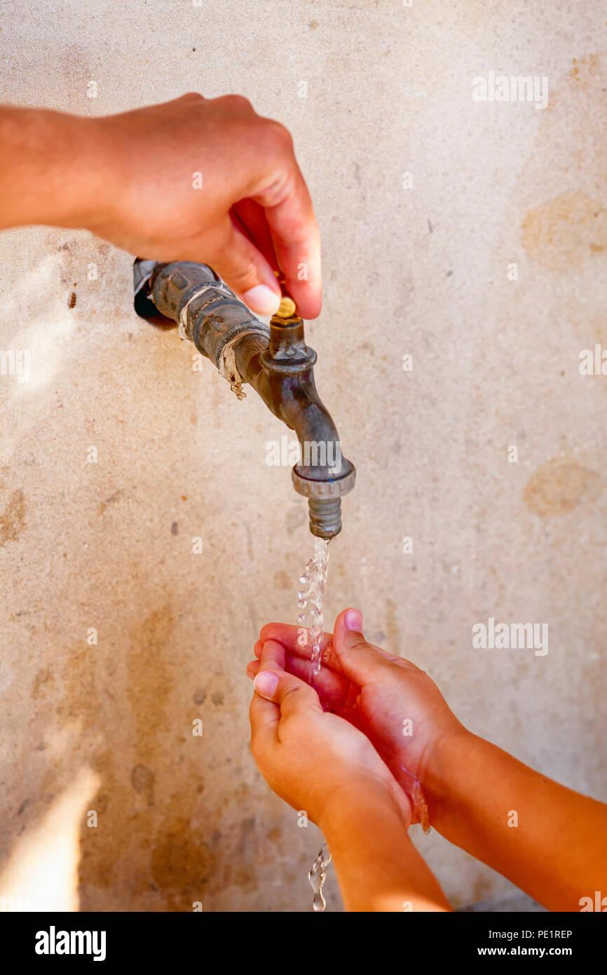 Donna aprire a mano il rubinetto dell'acqua e il bambino lavarsi le mani. Close up. Immagini Stock
