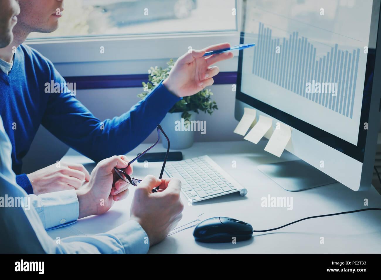 Un gruppo di giovani uomini di affari che colleghi cercando insieme al computer, il team di lavoro sul nuovo progetto di avvio in un ufficio moderno, il concetto di brainstorming Immagini Stock