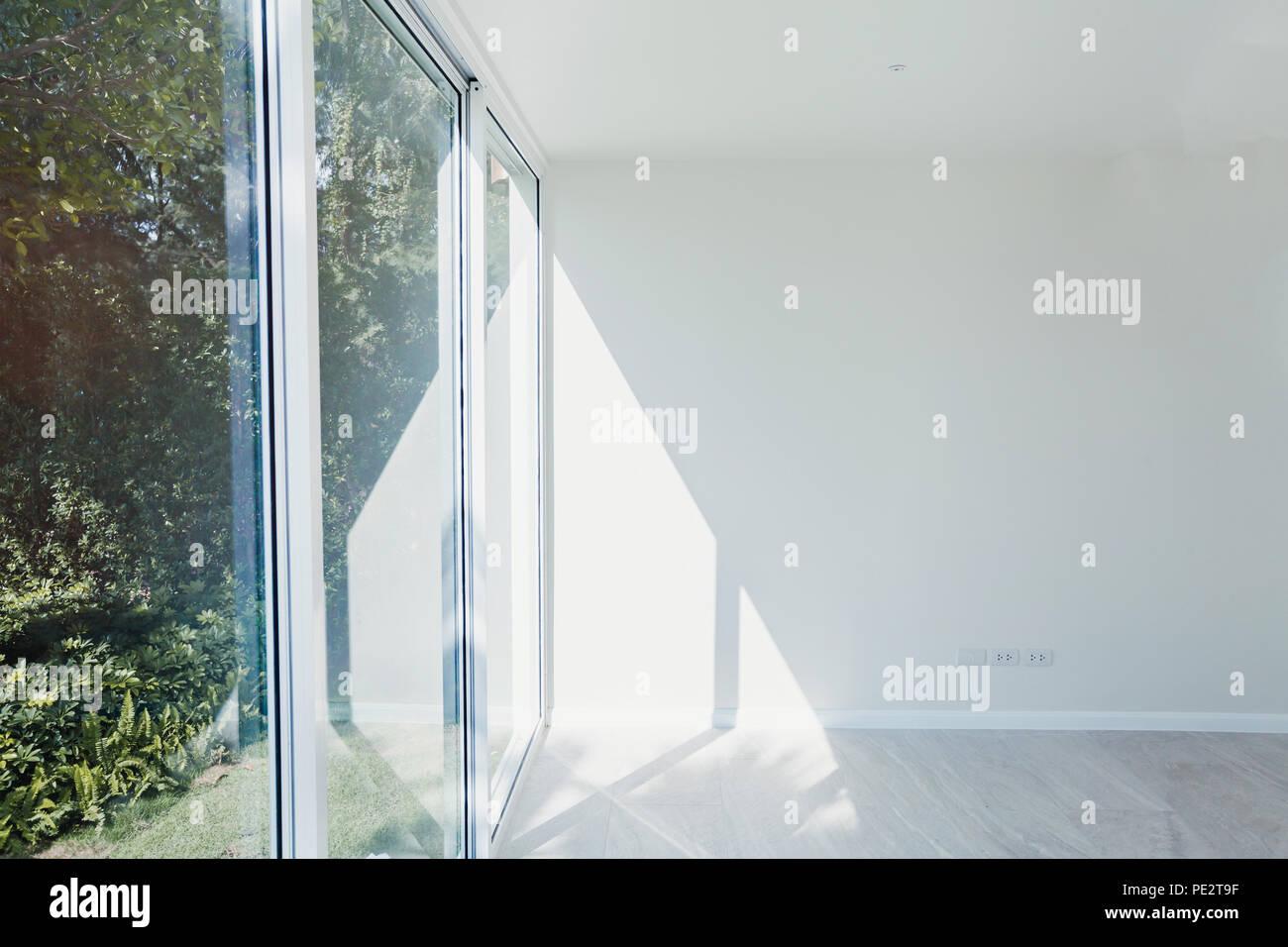 Svuotare soleggiata sala interna con il bianco parete dipinta, finestra grande e moderna con pavimento in legno parquet, nuovo appartamento in costruzione Foto Stock