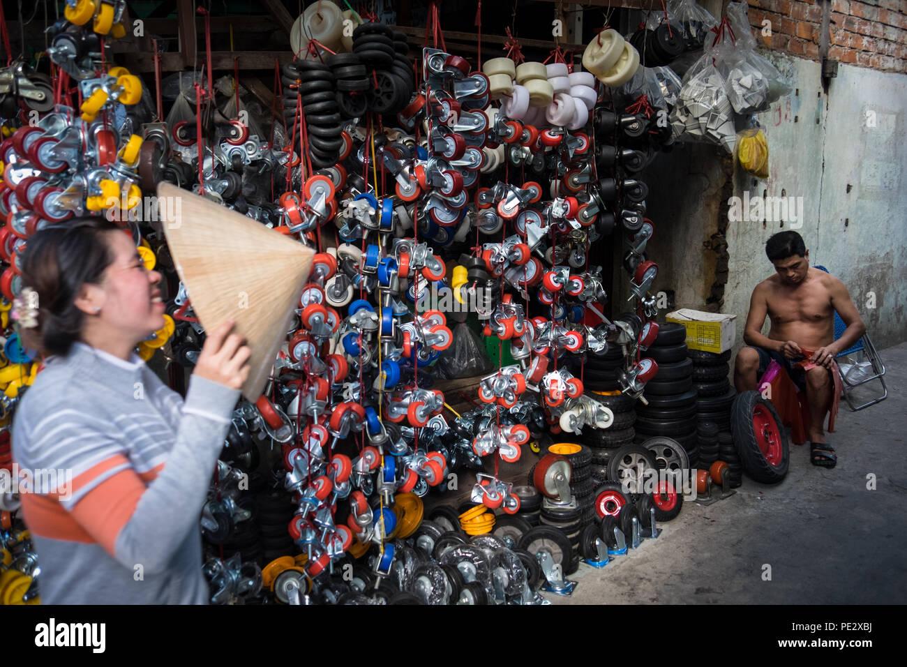 Un uomo vendita di ruote piroettanti in Cho un mercato Lac, Can Tho, Vietnam Immagini Stock