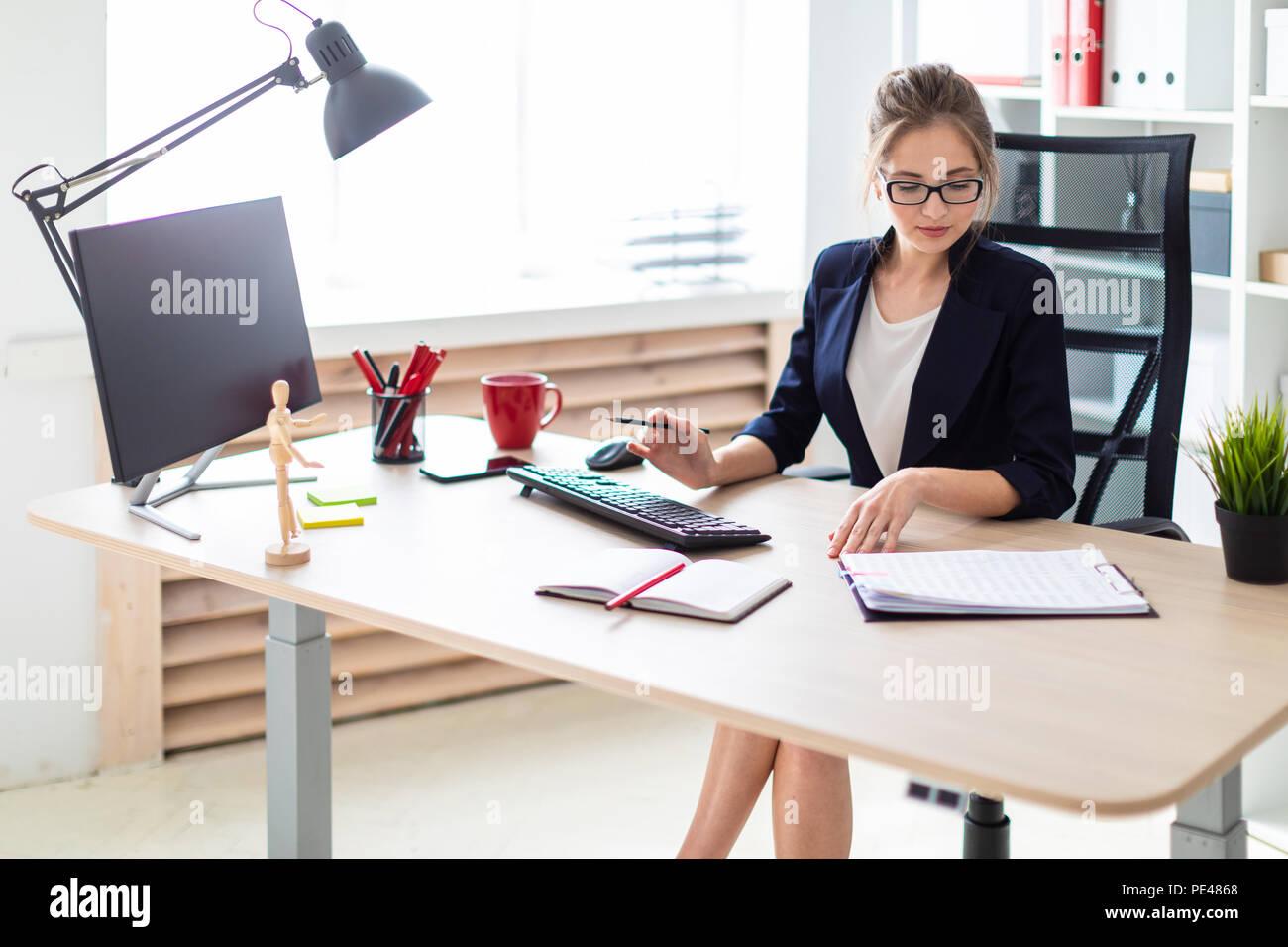 Una giovane ragazza è seduta a una scrivania per computer, tenendo in mano una matita in mano e lavorare con documenti. Immagini Stock