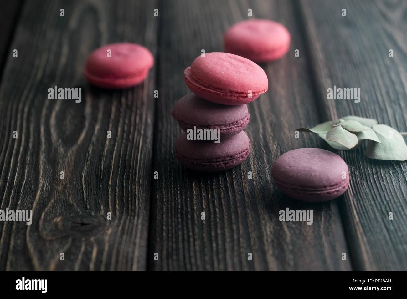 Gruppo di macarons fatta di fragole, crema, cioccolato e mirtilli. Foto rustico. Tonica. Immagini Stock