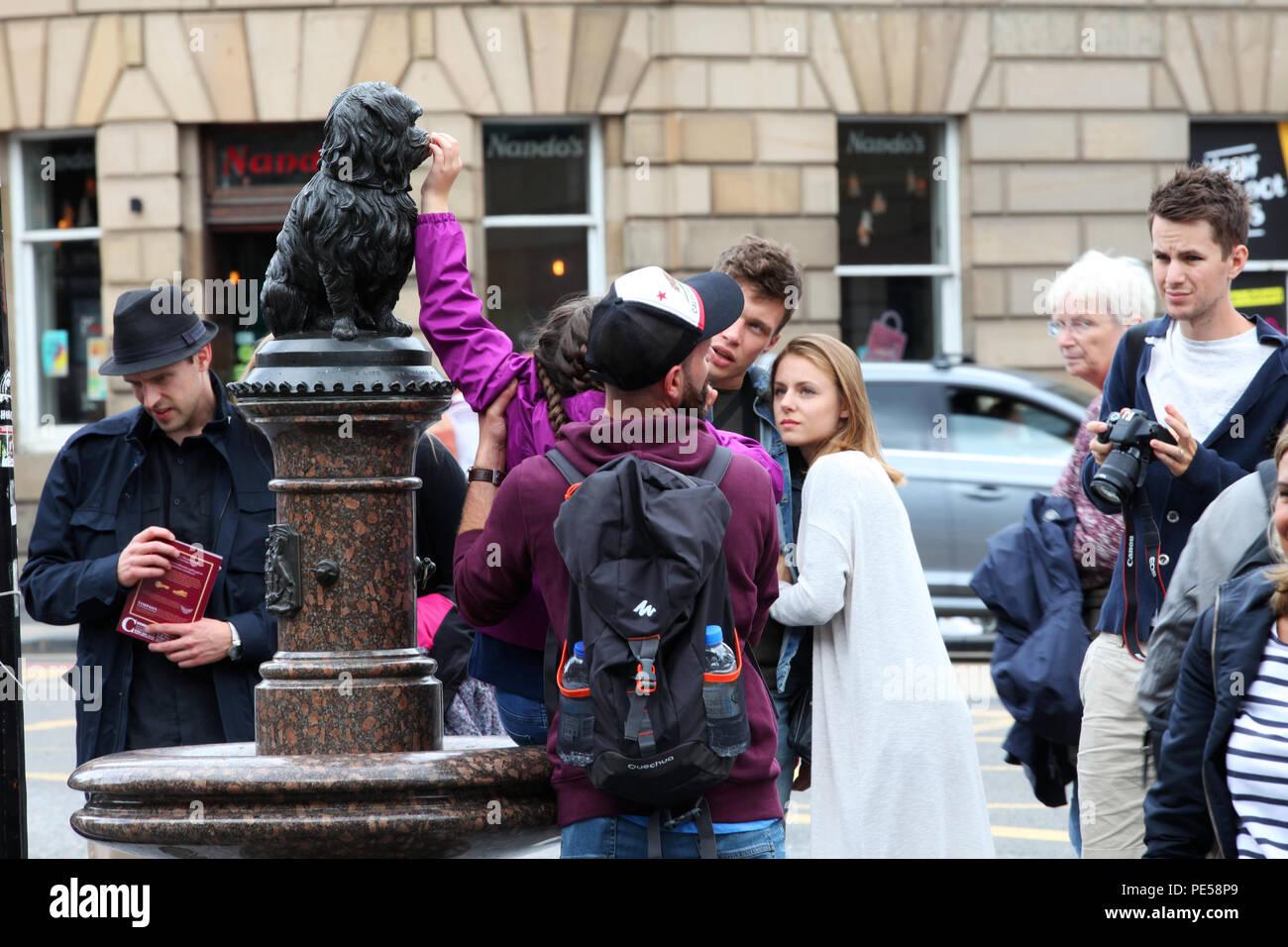 Un bambino è sollevato fino a toccare il naso sulla statua di Greyfriars Bobby in Edinburgh Immagini Stock