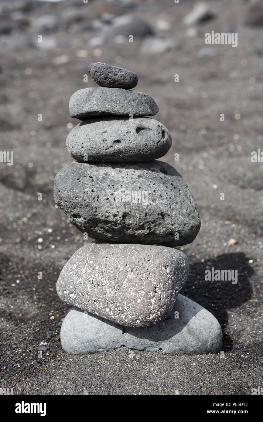 Impilati equilibrata di sassi o ciottoli su una spiaggia di sabbia nera. Immagini Stock