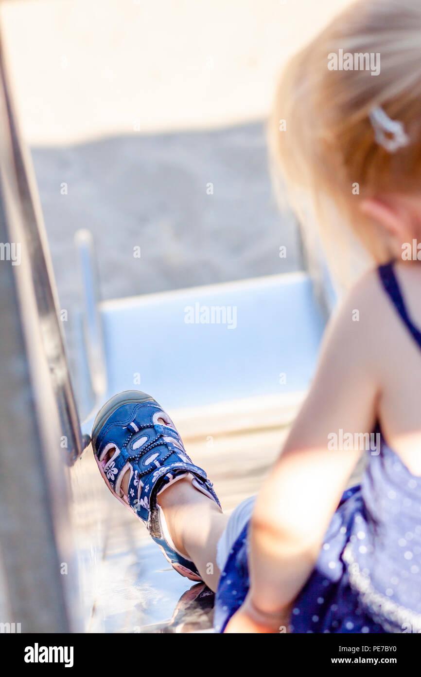 Carino bambina avendo divertimento sulla slitta a un parco giochi all'aperto in estate. Immagini Stock