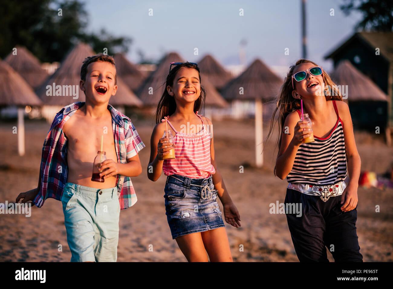 Felice bambini divertirsi mentre si cammina lungo una spiaggia di sabbia. Estate e concetto di viaggio Immagini Stock