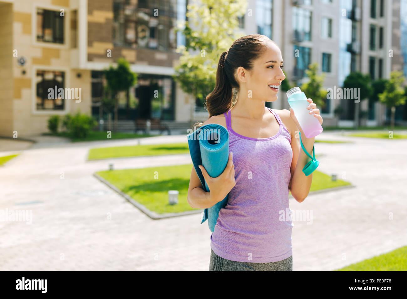 Gioiosa donna felice tiene una bottiglia di acqua Immagini Stock