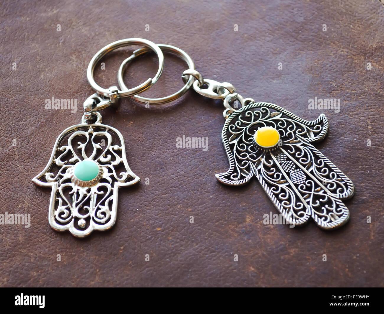 Chiave di due anelli in forma di Fatima la mano sulla pelle marrone dello sfondo. Simbolo di antico e di moderno e tradizionale souvenir turistici della Tunisia. Immagini Stock
