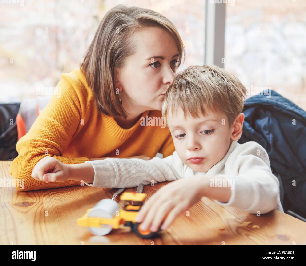 Ritratto di white Caucasian famiglia felice, madre e figlio seduti al ristorante cafe a tavola, kissing giocando con il giocattolo auto, autentico stile di vita Immagini Stock