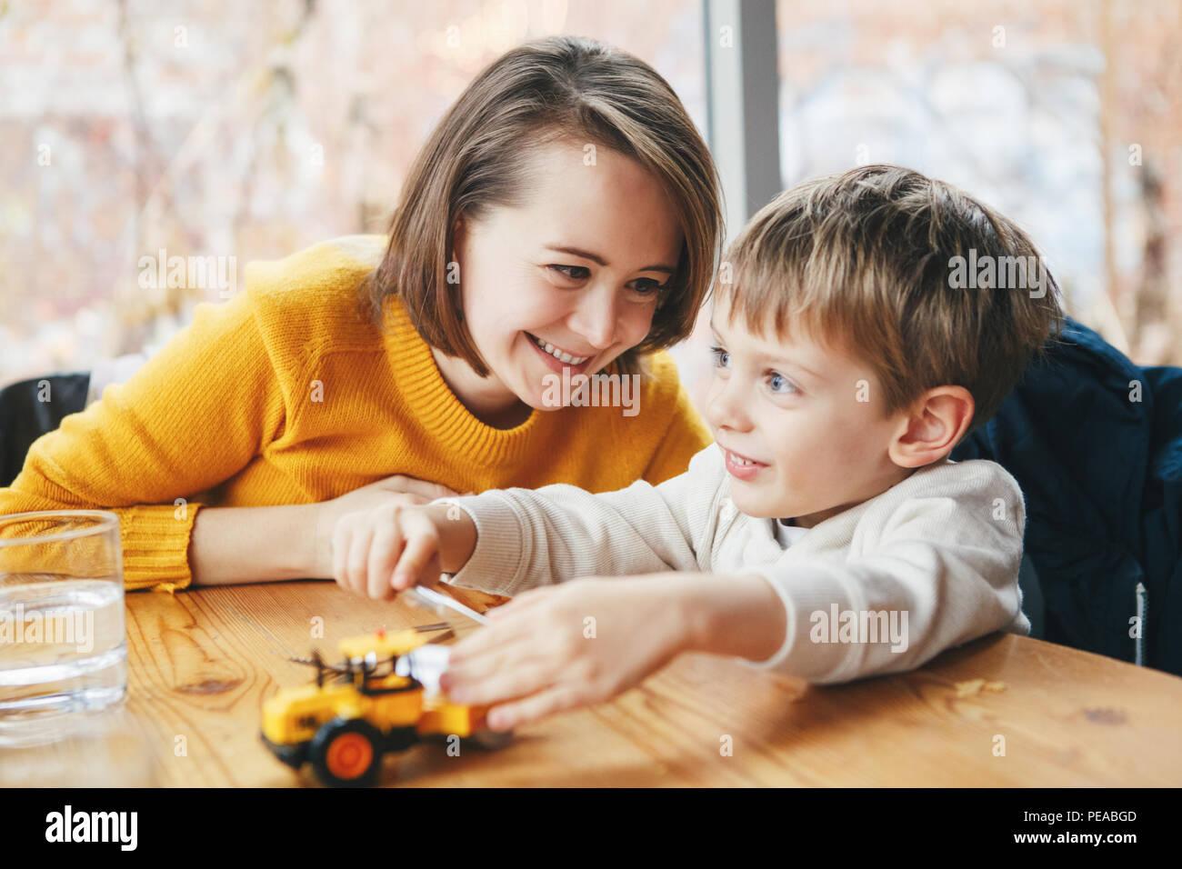Ritratto di white Caucasian famiglia felice, madre e figlio seduti al ristorante cafe a tavola, sorridente giocando con il giocattolo auto, autentico stile di vita Immagini Stock