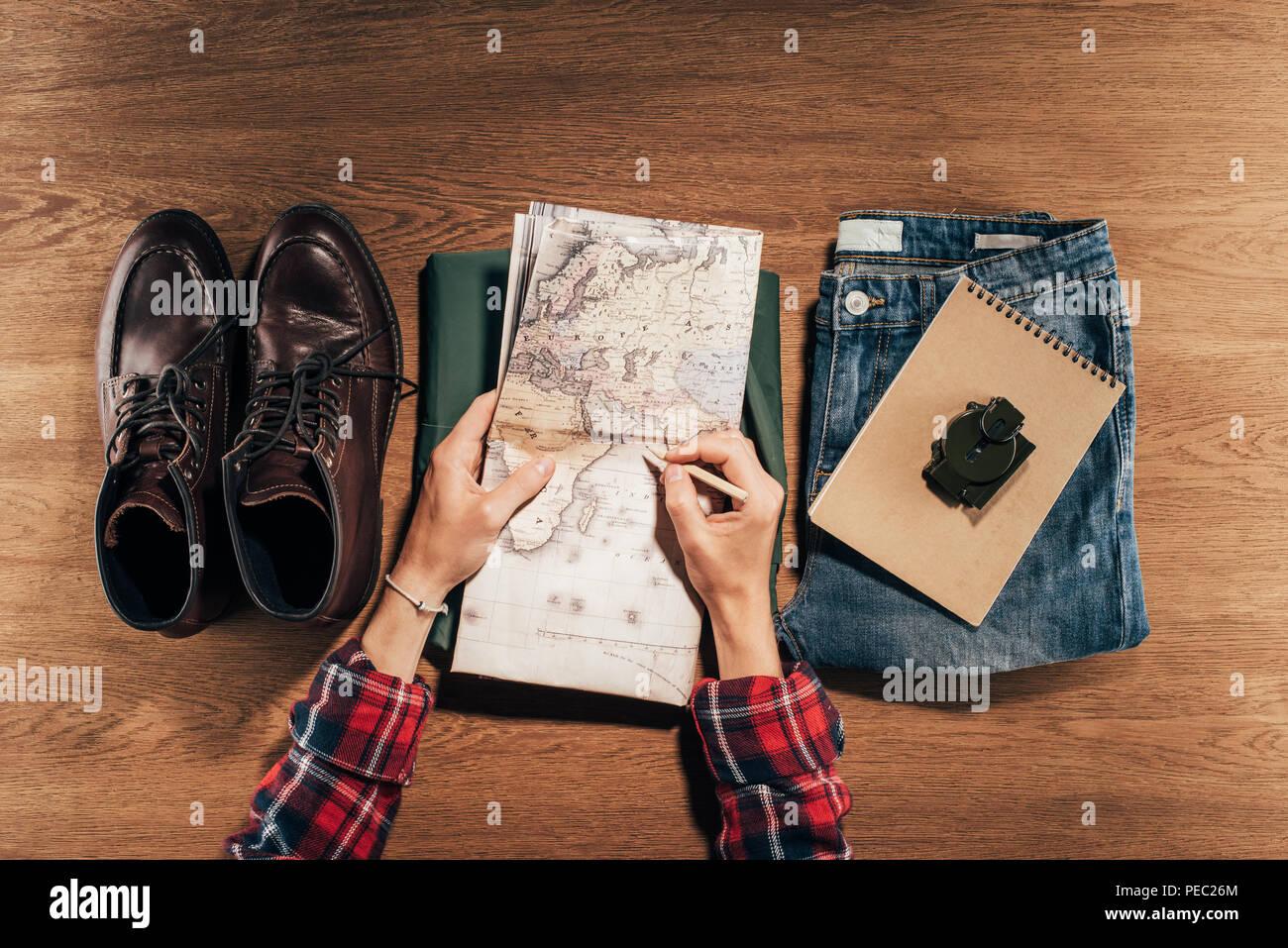 Vista in pianta parziale della persona in possesso di mappa e traveler impostato sul tavolo di legno Immagini Stock