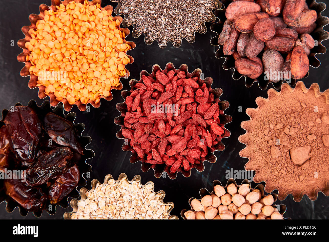 Varie superfoods in una piccola ciotola su blackbackground. Super come chia, materie fava di cacao, goji, ceci, lenticchie. Copia dello spazio. Lay piatto. Immagini Stock