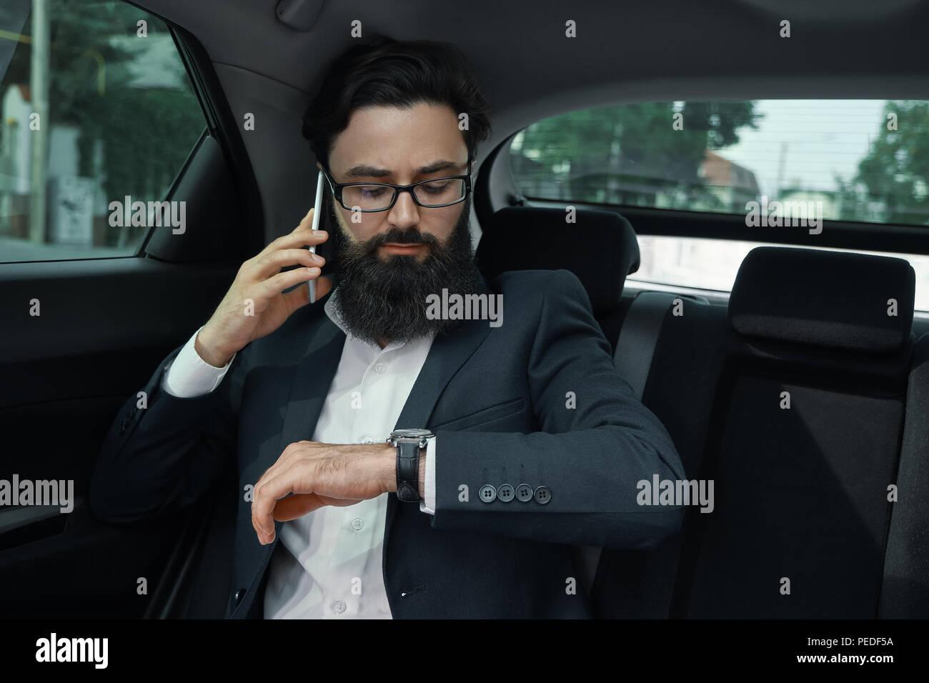 Un imprenditore durante un viaggio in auto nel sedile posteriore utilizzando una sm Immagini Stock