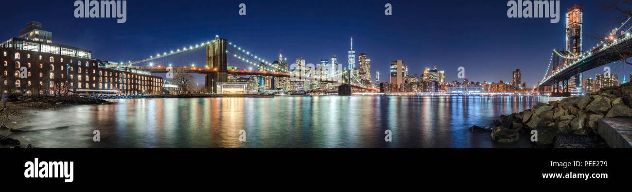 I grattacieli di Manhattan, il Ponte di Brooklyn e il Manhattan Bridge in serata con la East River (panoramico). La città di New York Immagini Stock