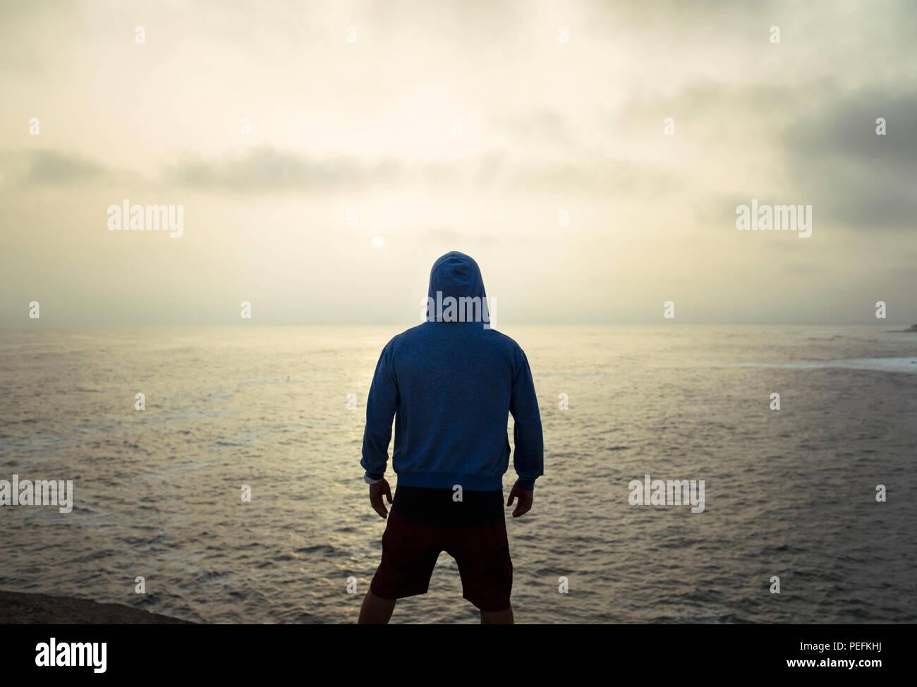 Silhouette di un uomo in una felpa con cappuccio da dietro a guardare il tramonto dorato oltre oceano. Punta Hermosa surfisti (città), Provincia di Lima, Perù. Lug 2018 Immagini Stock