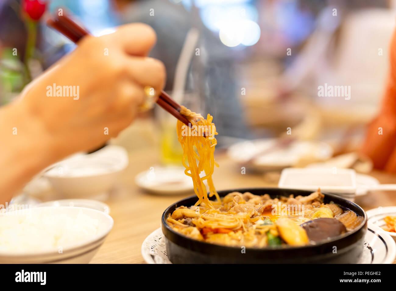 Mano con bacchette di mangiare giapponese udon noodles. Foto Stock