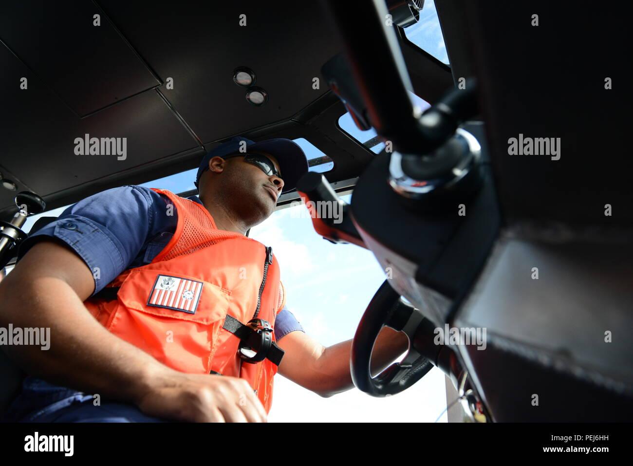 Petty Officer di terza classe Lowell Belany, una riserva di boatswain mate fuori della stazione della Guardia Costiera Vallejo, California, prende il timone durante la navigazione i punti sulla linea di rotta lungo il fiume Columbia durante la riserva nocchiero College di Portland, Ore., 28 agosto 2015. Gli studenti che frequentano il collegio erano tenuti a plot e navigare verso waypoint utilizzando diversi sulla terra dei punti di riferimento lungo il fiume Columbia. (U.S. Coast Guard foto di Sottufficiali di terza classe Jonathan Klingenberg) Immagini Stock
