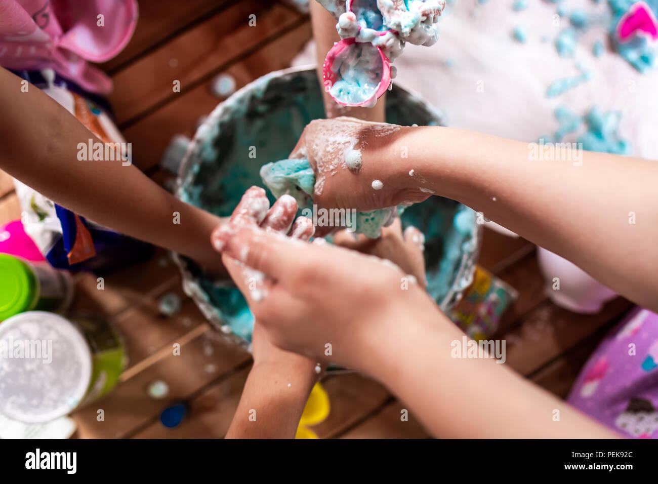 Un gruppo di giovani ragazze, i bambini fanno un pasticcio con spuma slime ad una festa di compleanno Immagini Stock