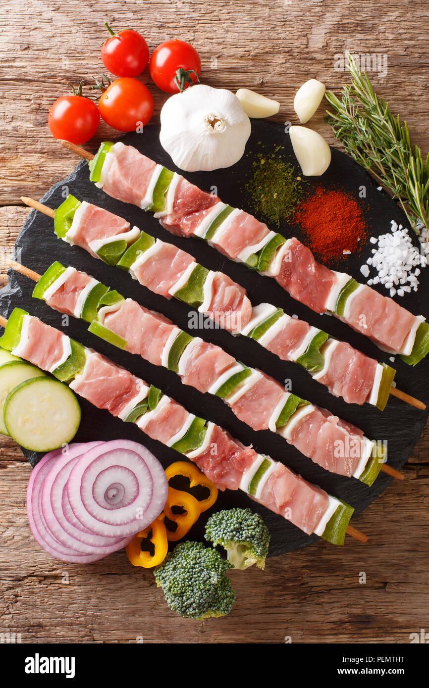 Per barbecue materie shish kebab con pepe e lo strutto su spiedini di close-up e ingredienti, verdure, spezie, erbe sul tavolo. Verticale in alto vista dal Immagini Stock