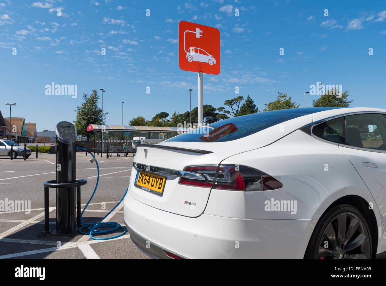 Auto elettrica inserita in un punto di carica. Il veicolo elettrico collegato ad un condotto di carica nel West Sussex, in Inghilterra, Regno Unito. Immagini Stock