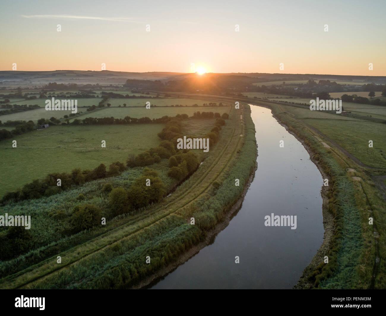 Drone foto oltre il Fiume Arun nel West Sussex attraverso il tramonto su un paesaggio inglese. Foto Stock
