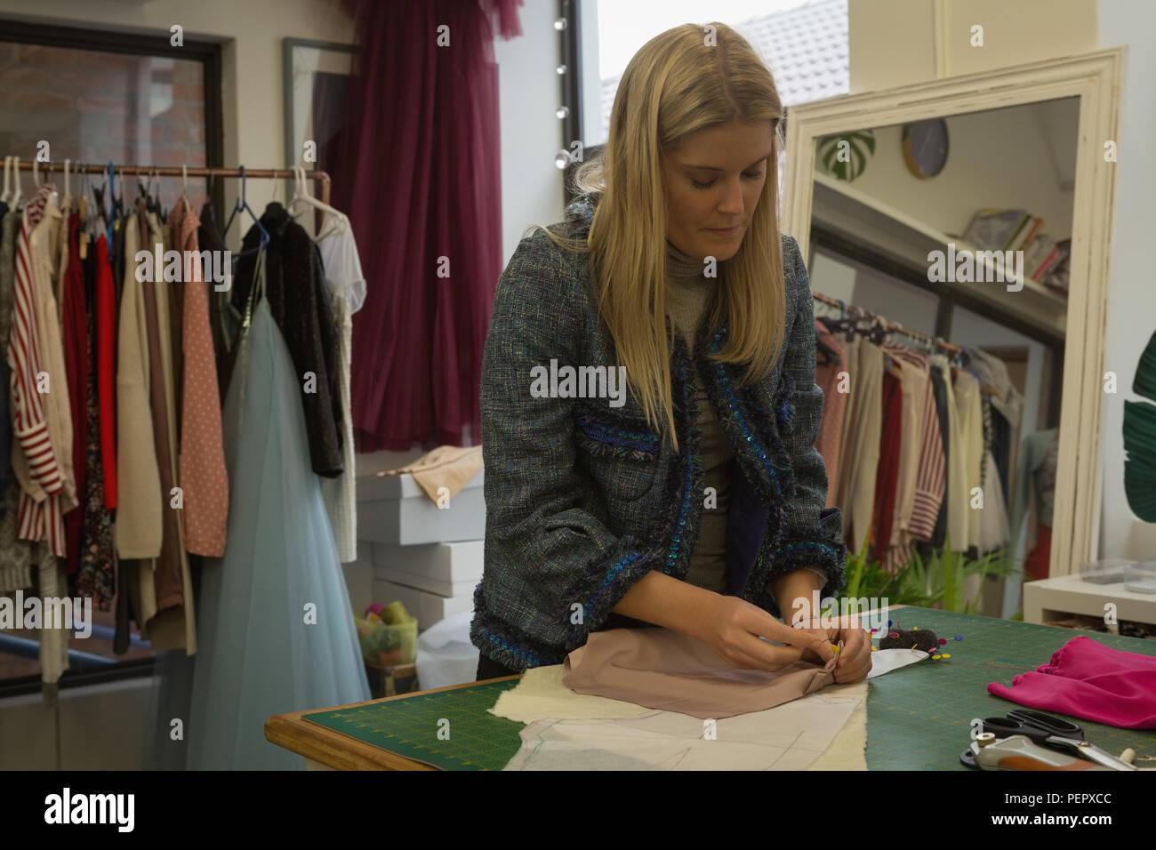 Designer di moda pinning su tessuto di moda studio Immagini Stock