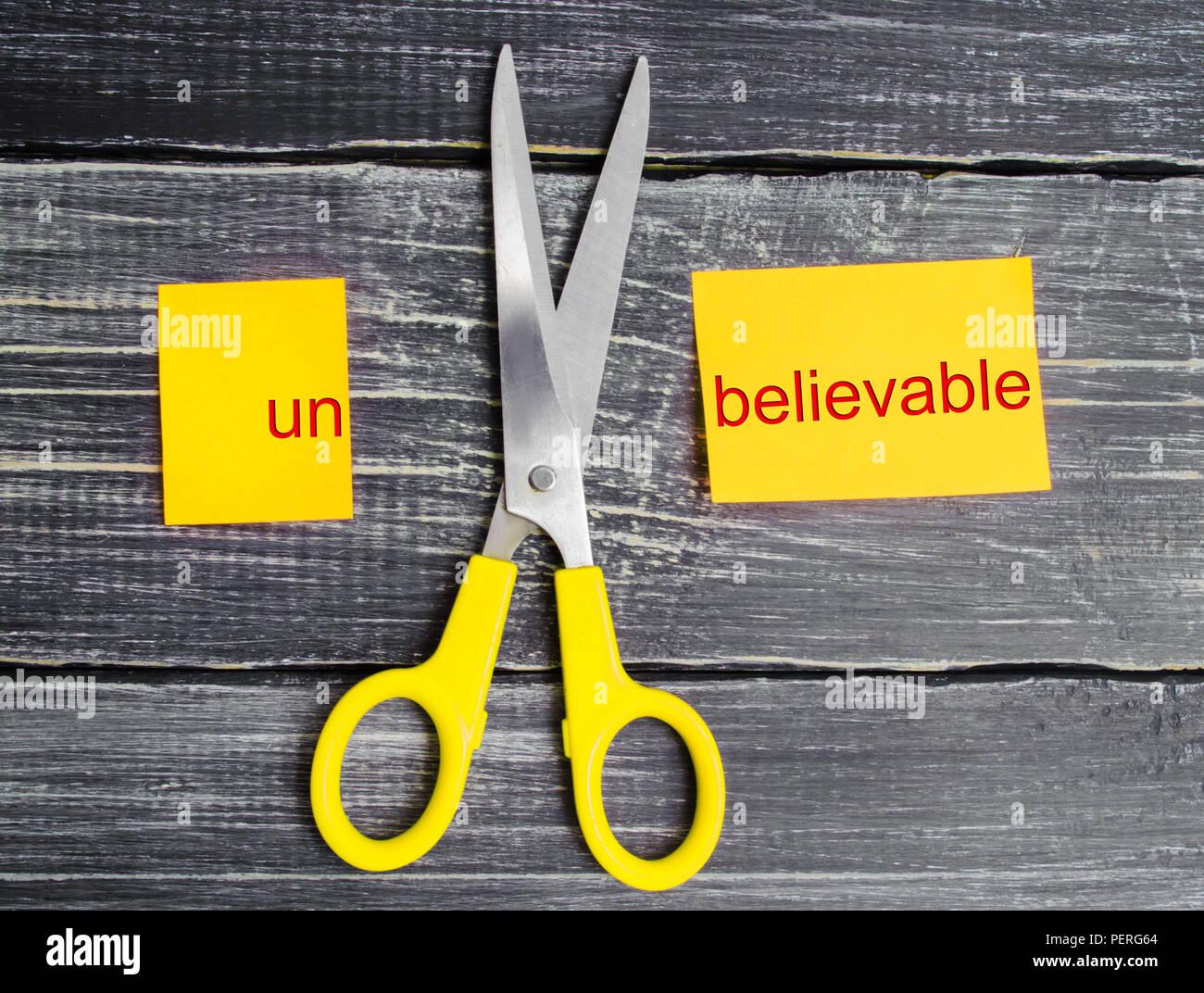 """Forbici battono la parola incredibile. concetto credibile. Tagli la parola 'ONU. """"Posso, raggiungimento degli obiettivi potenziali di superamento Immagini Stock"""