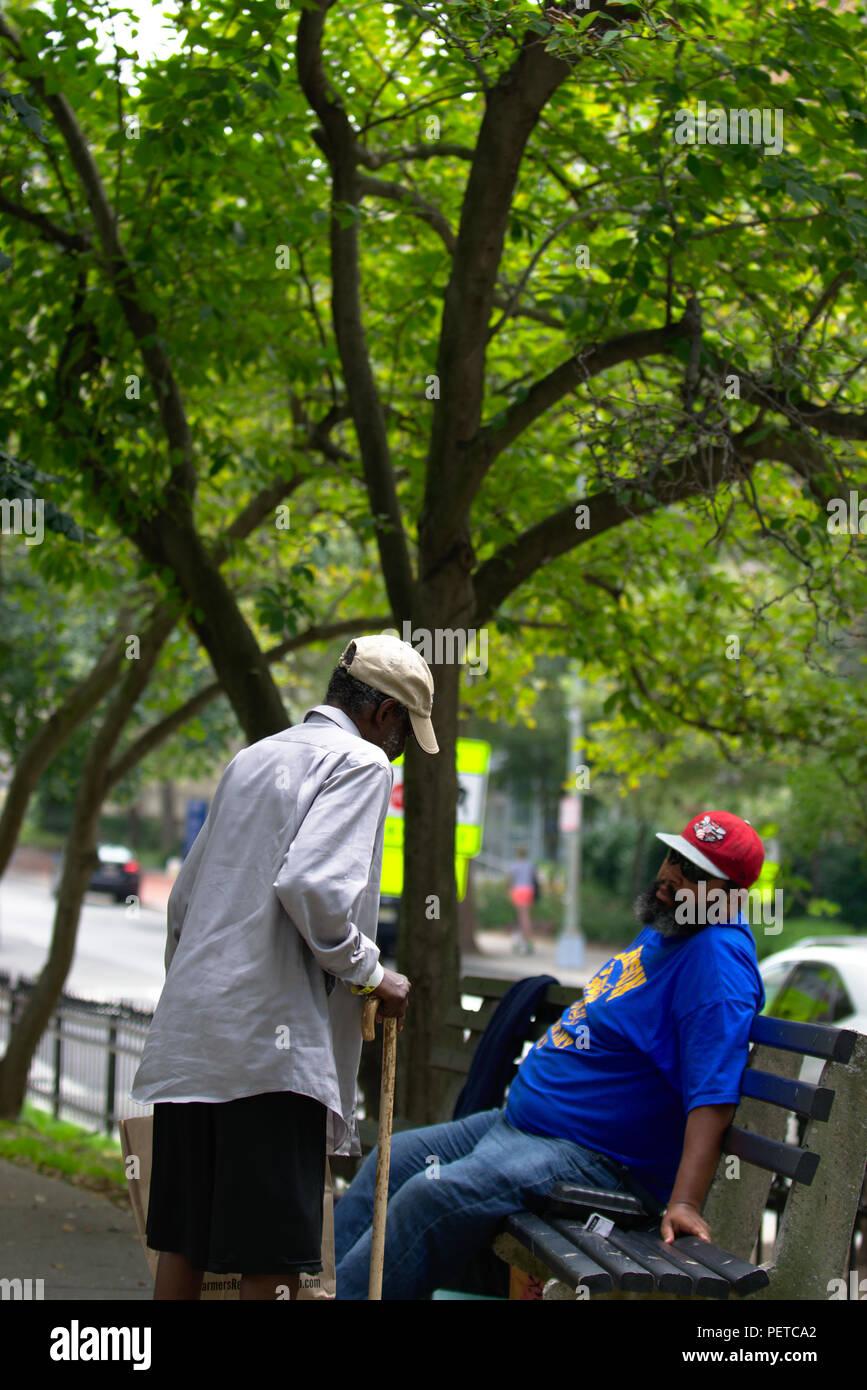 Due senzatetto americano africano gli uomini uno in piedi con la canna da zucchero altra seduta sul banco di lavoro Immagini Stock