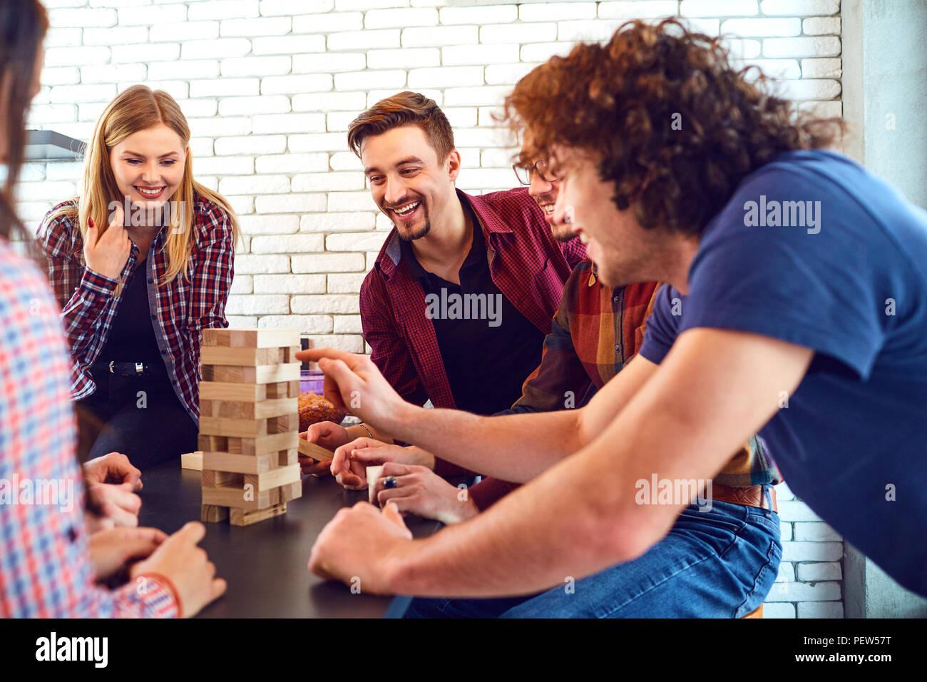 Un vivace gruppo di giovani giocare a giochi da tavolo. Immagini Stock
