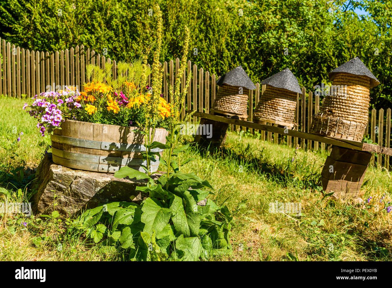 Tre piccoli alveari e un vaso con fiori colorati. il giardino è