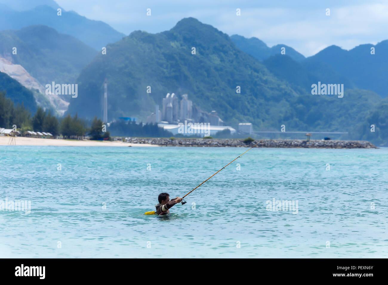 Pescatore in mare con la canna da pesca 34e436d9628a